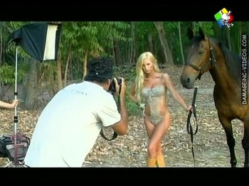 blonde in bikini posing by a horse